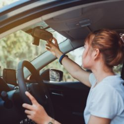 Safety driving woman adjust the car rearview mirror in interior before start travel trip every time.